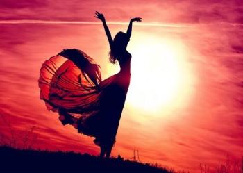 На фоне заката силуэт танцующей девушки