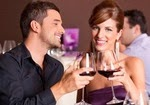 Влюбленные за столиком в ресторане с бокалами вина