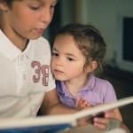 Брат читает сестре книжку