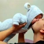 папа целует ребенка в пижамке