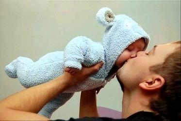 папа целует малыша в пижамке