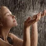 Девушка подставляет руки под струи дождя